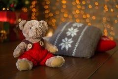 长毛绒棕熊在背景bokeh的圣诞树下 免版税库存照片