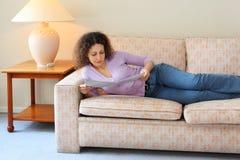 长沙发位于空间简单的妇女 库存照片