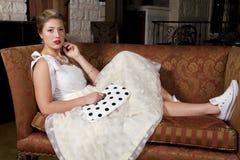 长沙发佩带的网球鞋的年轻新娘 库存照片