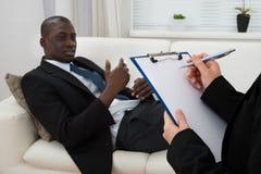 长沙发和精神病医生文字的患者在剪贴板 图库摄影