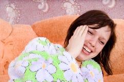 长沙发哭泣的女孩是 库存图片