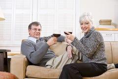 长沙发夫妇放松的前辈一起喝酒 免版税库存图片