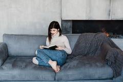 长沙发女孩开会 顶楼样式的室 有壁炉的室 登记女孩读取 有一本书的一个女孩在 免版税图库摄影