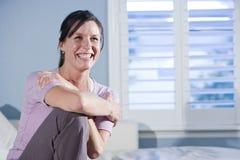 长沙发愉快的坐的微笑的妇女 免版税库存图片