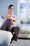 长沙发愉快的坐的微笑的妇女 免版税图库摄影