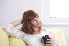 长沙发放松的女孩 免版税库存图片