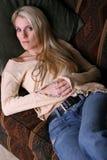 长沙发的三金发碧眼的女人 图库摄影