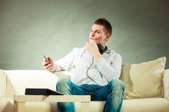 长沙发的人有耳机的智能手机和片剂 免版税库存照片