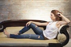 长沙发的可爱的妇女 库存照片