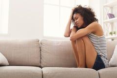 长沙发的哀伤的非裔美国人的妇女在家 免版税库存照片