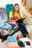 长沙发的女孩在行李附近 免版税库存照片