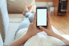 长沙发的女孩有电话的在手中 库存照片