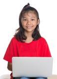 长沙发的女孩有膝上型计算机的II 免版税库存照片