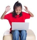长沙发的女孩有膝上型计算机的v 免版税库存图片