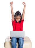 长沙发的女孩有膝上型计算机的VI 免版税图库摄影