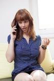 长沙发的女孩谈话在电话 库存照片