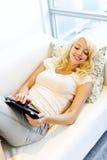 长沙发的妇女与片剂计算机 库存图片