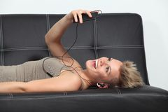 长沙发的妇女在家听到从智能手机的音乐的 免版税库存图片