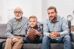 长沙发的小男孩有,欢呼为橄榄球赛和举行a的祖父和父亲的 图库摄影