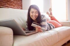 长沙发的微笑的亚裔妇女使用在网上购物的片剂 免版税库存图片