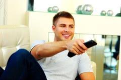 长沙发的微笑的人看电视的 免版税库存照片