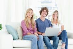 长沙发的微笑的人,他们使用膝上型计算机 免版税库存照片