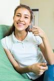 长沙发的微笑的少年女孩 库存图片
