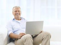 长沙发的微笑的老人 图库摄影