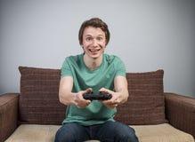 长沙发的快乐的游戏玩家 库存照片
