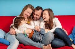 长沙发的愉快的父亲和女儿 图库摄影