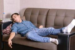 长沙发的睡觉的年轻人在屋子里,疲倦在工作以后,被喝在党以后 无论如何睡着了 库存照片