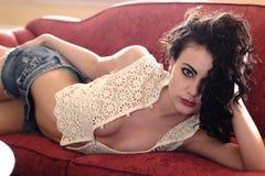 长沙发的美丽的女孩 库存图片