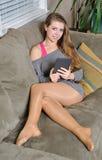 长沙发的美丽的少妇有e阅读程序的 免版税库存图片