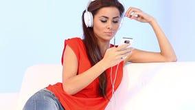 长沙发的逗人喜爱的女孩听到音乐 股票录像