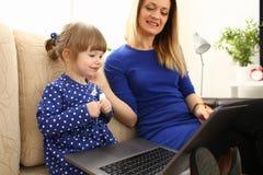长沙发的逗人喜爱的小女孩有妈妈用途膝上型计算机的 免版税库存照片