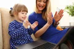 长沙发的逗人喜爱的小女孩有妈妈用途膝上型计算机的 免版税库存图片