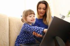 长沙发的逗人喜爱的小女孩有妈妈用途膝上型计算机的 库存图片