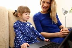 长沙发的逗人喜爱的小女孩有妈妈用途膝上型计算机的 库存照片