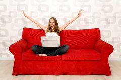 长沙发膝上型计算机坐的妇女 免版税库存照片