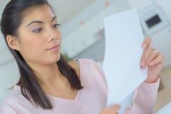 长沙发读书信件的妇女 库存图片