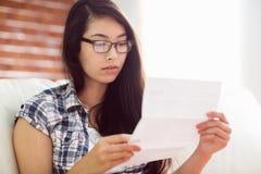 长沙发读书信件的亚裔妇女 免版税库存图片