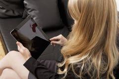 长沙发work´s的妇女与片剂个人计算机 免版税库存图片