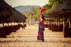 长波大红色帽子的亭亭玉立的女孩在芦苇伞中 免版税库存图片