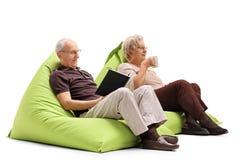 年长男人和妇女坐装豆子小布袋 免版税库存照片