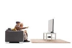 年长男人和妇女坐长沙发和观看的电视 免版税库存照片