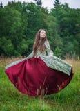 长的中世纪礼服跳舞的美丽的愉快的妇女 免版税库存照片