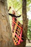 长的五颜六色的礼服立场的Boho女孩在树在公园夏天d 图库摄影