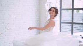 长的典雅的白色豪华礼服旋转的艺术性的女孩在宽敞的房间,恳切地微笑,并且快乐,培养她 股票录像