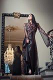 长的典雅的黑礼服的年轻美丽的豪华妇女。有大镜子的深色的妇女在背景中。诱人的浅黑肤色的男人 免版税库存照片