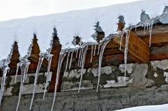 长的冰柱从在砖墙上的屋顶垂悬 免版税库存图片